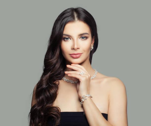 mujer de la joyería. mujer joven con maquillaje, largo y rizado pelo y diamante anillo, collar y pendientes - joyas fotografías e imágenes de stock