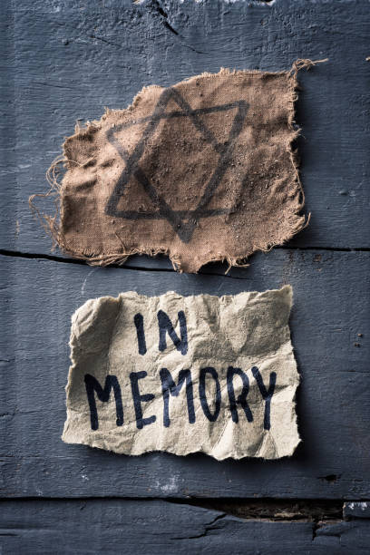 jewish badge and text in memory in piece of paper high angle view of a ragged jewish badge and a yellowish piece of paper with the text in memory written in it, on a gray rustic wooden surface mass murder stock pictures, royalty-free photos & images