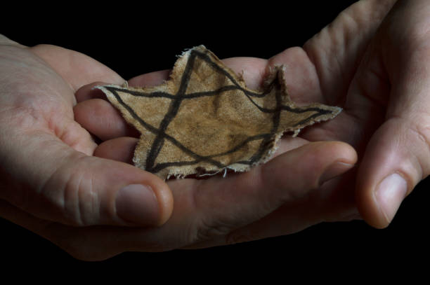 Jewish badge in the hands of a man Closeup of a ragged Jewish badge in the hands of a man judaism stock pictures, royalty-free photos & images