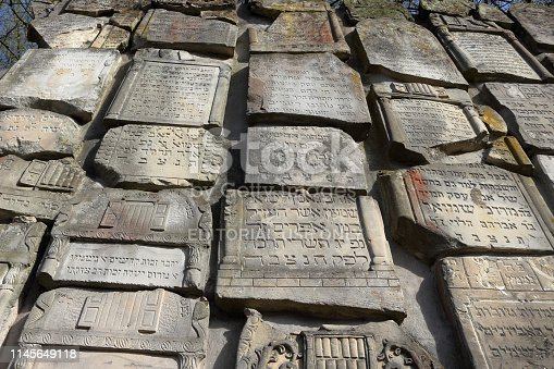 Kazimierz Dolny, Poland - April 17, 2019: Part of monument, lapidarium, wailing wall, in Jewish cemetery in Czerniawy, built from surviving headstones of Jewish graves mostly destroyed during the second world war and now commemorating Jewish population of Kazimierz Dolny, Poland.