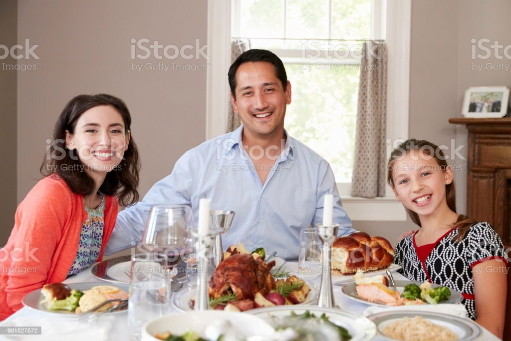 Jewish family at Shabbat dinner table smiling to camera stock photo