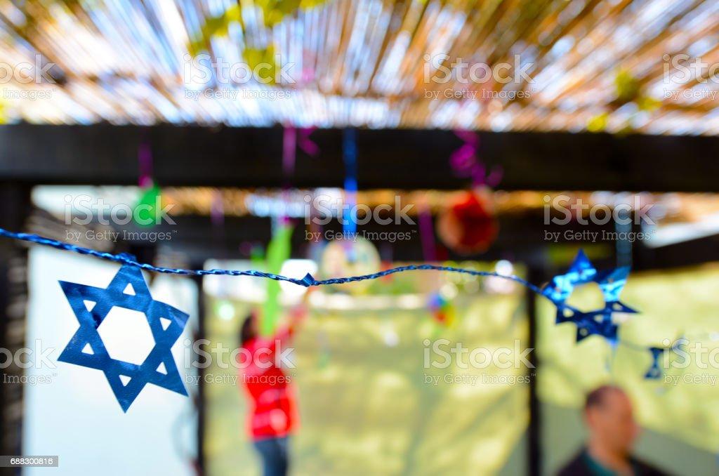 Jewish family decorating Sukkah for the Jewish festival of Sukkot stock photo
