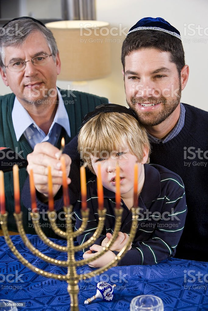 Jewish family lighting Chanukah menorah stock photo