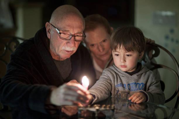 żydowska rodzina oświetlenie chanuka świece w menory na święta - judaizm zdjęcia i obrazy z banku zdjęć
