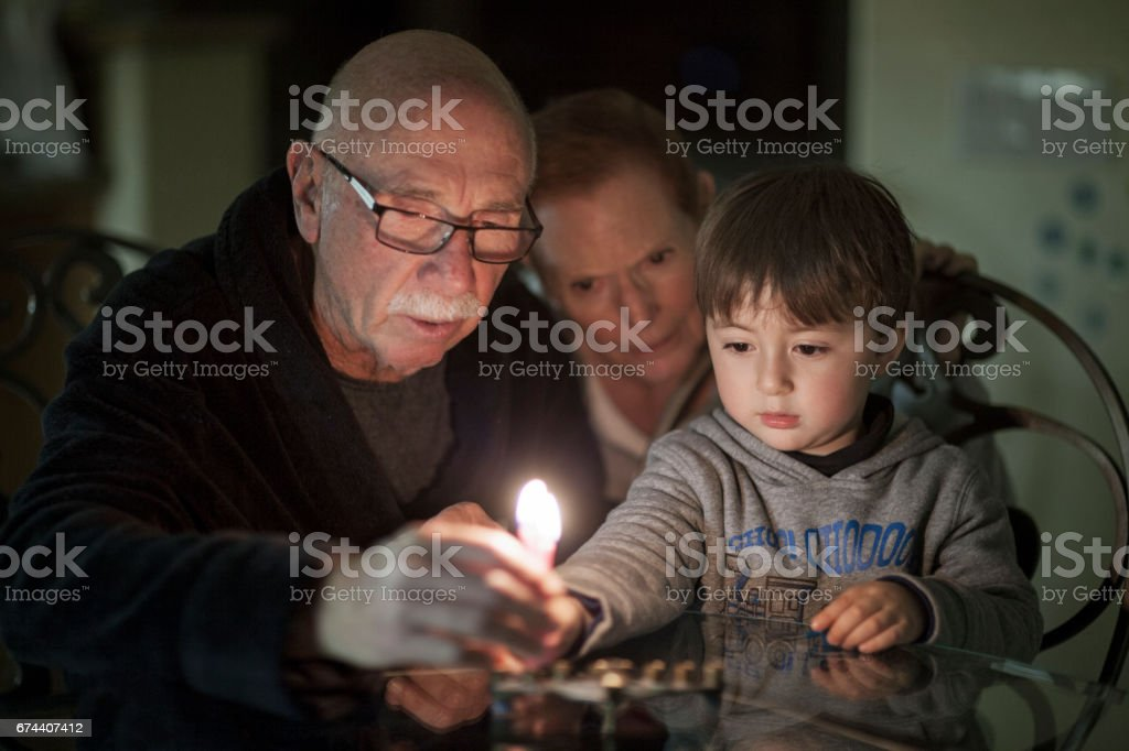 Jewish Family lighting Hanukkah Candles in a menorah for the holidays stock photo