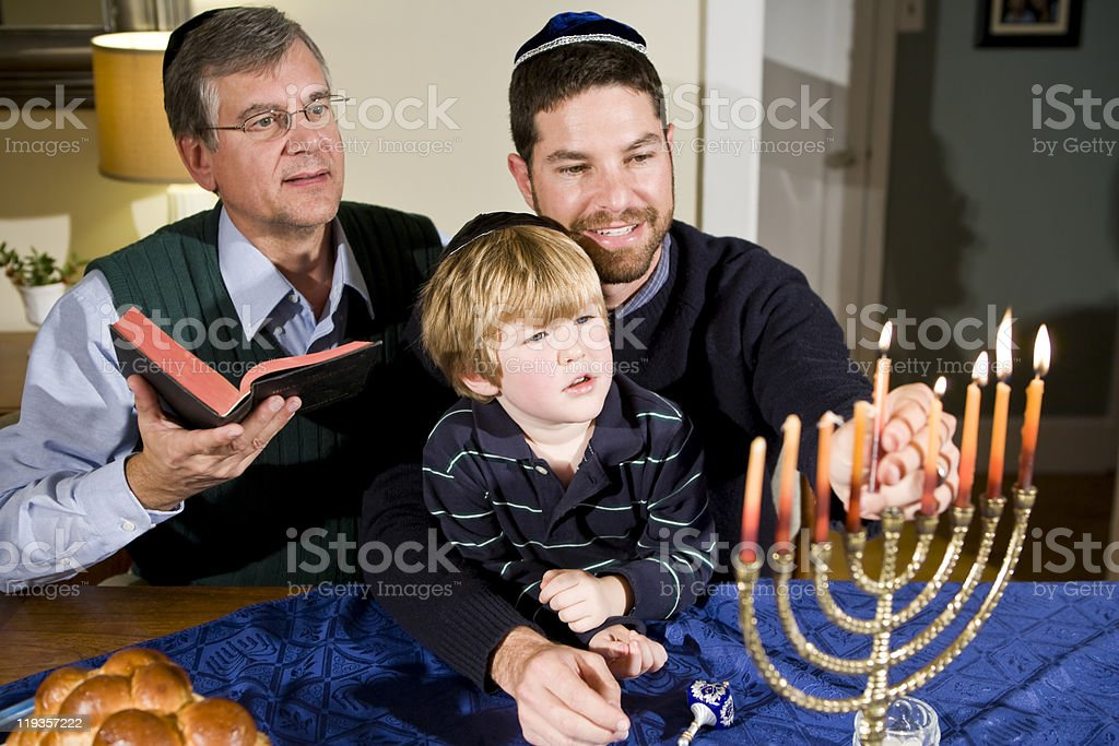 Jewish family lighting Hanukkah menorah royalty-free stock photo