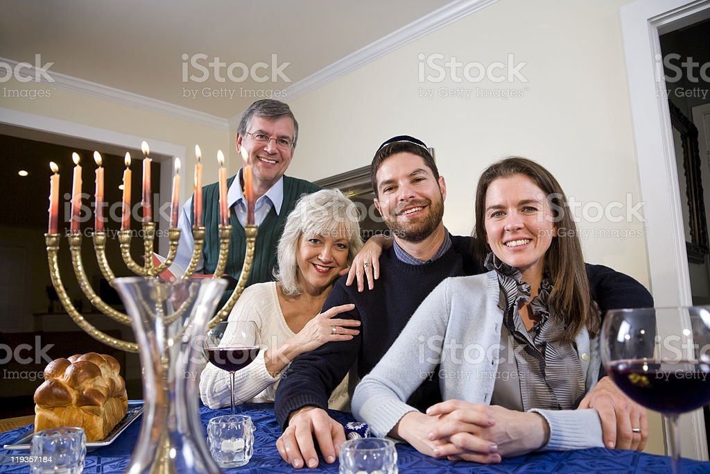 Jewish family smiling and celebrating Hanukkah at the table stock photo