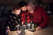 Jewish Family with granparents and grandson lighting Hanukkah Candles in a menorah for the holidays