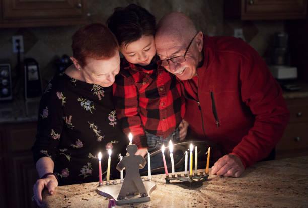 żydowska rodzina z granparents i wnuk oświetlenie chanuka świece w menory na święta - judaizm zdjęcia i obrazy z banku zdjęć