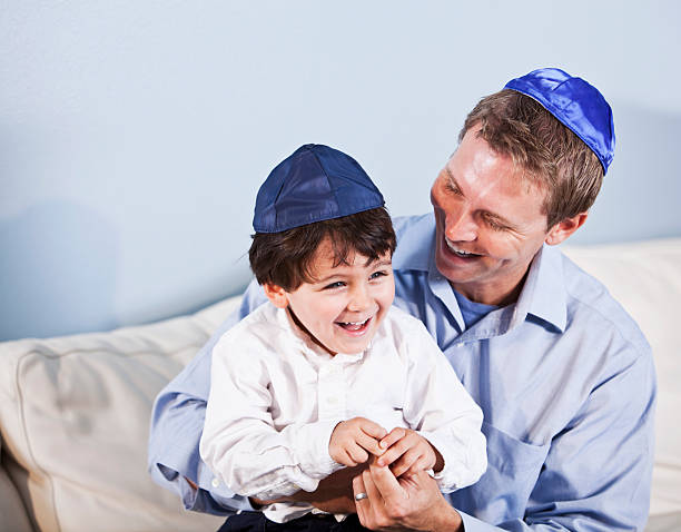 Jewish father and little boy laughing Jewish father (30s) and son (3 years) sitting together, laughing. judaism stock pictures, royalty-free photos & images
