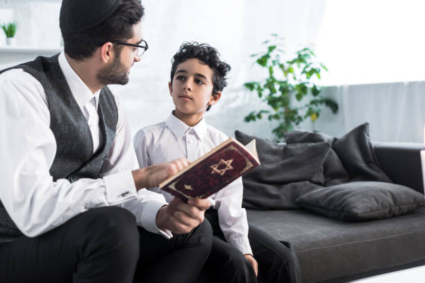 jewish father and son talking and holding tanakh in apartment jewish father and son talking and holding tanakh in apartment judaism stock pictures, royalty-free photos & images