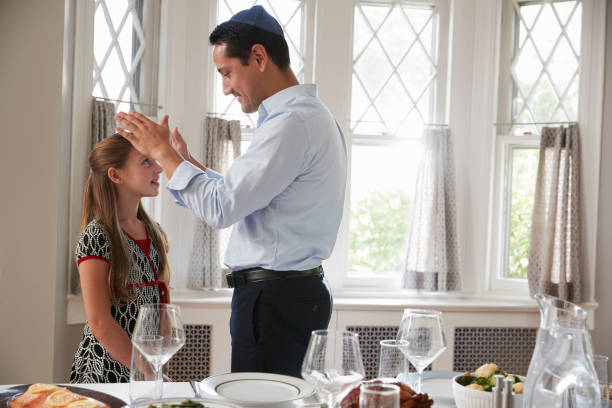 Jewish father blesses daughter by table set for Shabbat meal stock photo
