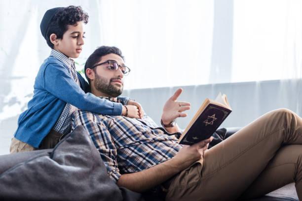 żydowski ojciec wskazując ręką na tanakh i rozmawiając z synem w mieszkaniu - judaizm zdjęcia i obrazy z banku zdjęć