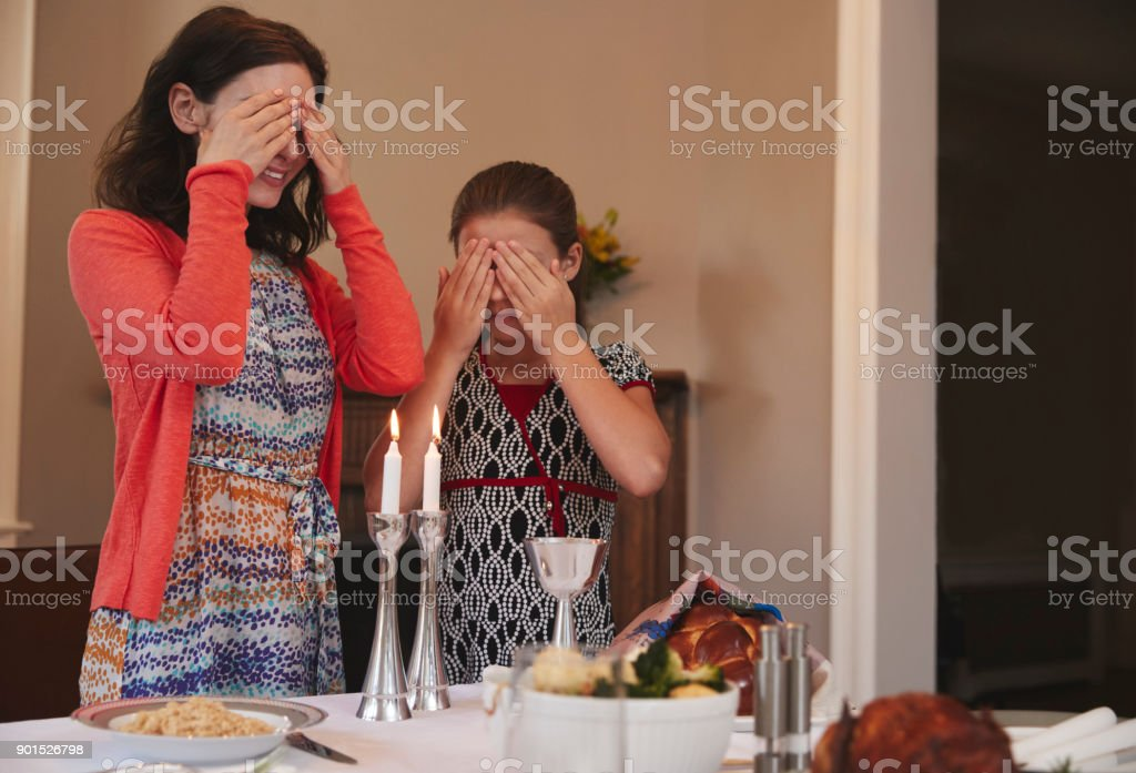 Jewish girl and mother cover eyes to recite Shabbat blessing stock photo