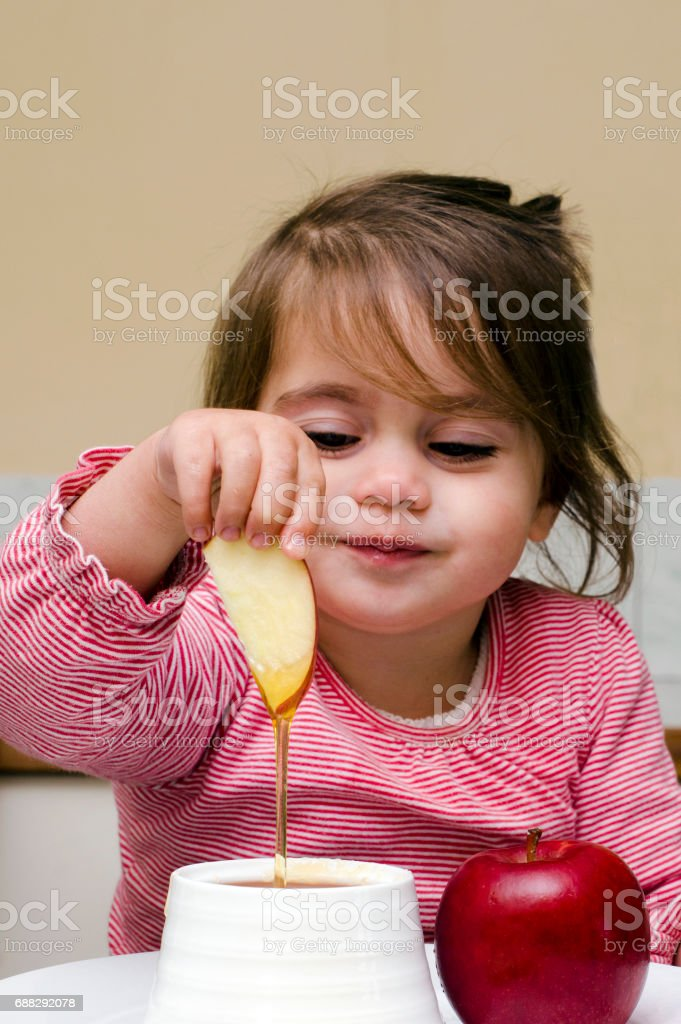 Jewish girl dipping apple slices into honey stock photo