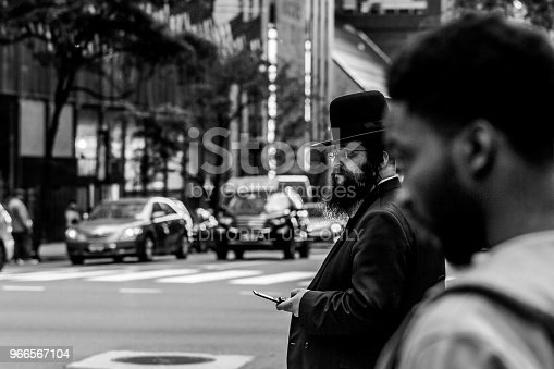 New York, United States - May 30, 2018: Young traditionally dressed hassidic man walks, crossing the street in the opposite direction.