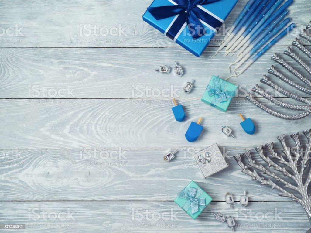 Jewish holiday Hanukkah background with menorah, gift box and dreidel...