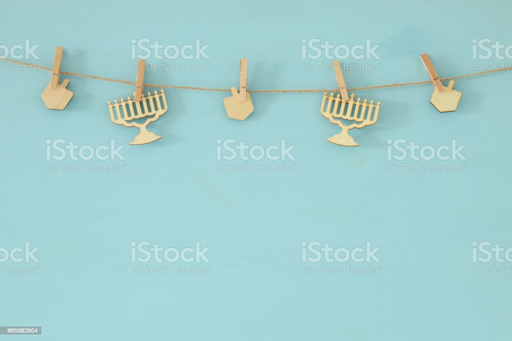 jewish holiday Hanukkah background with decorative wooden menorah (traditional candelabra) and spinning tops hanging on a rope stock photo