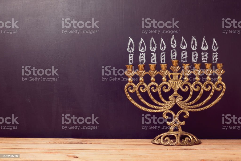 Jewish holiday Hanukkah background with menorah over chalkboard with...