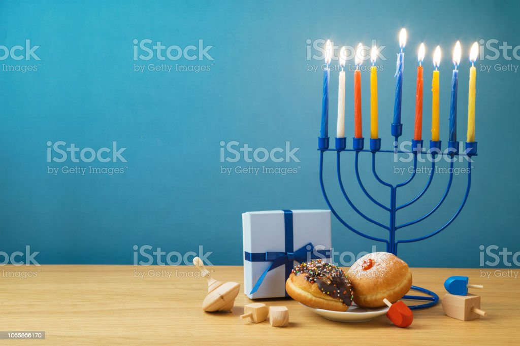 Jewish holiday Hanukkah background with menorah, sufganiyot, gift box...