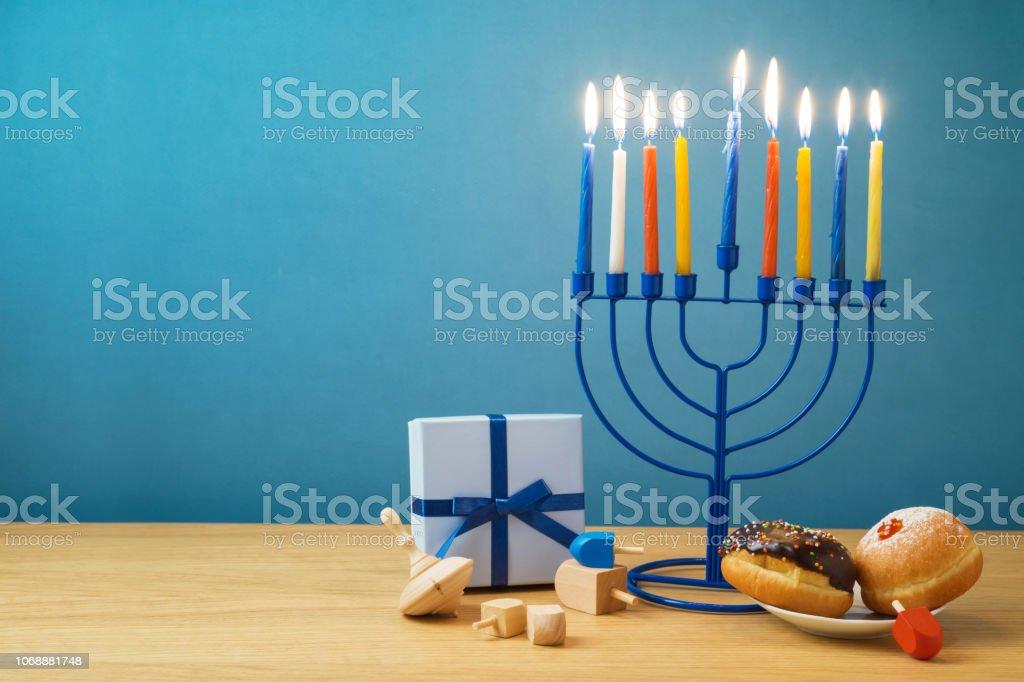 Jewish holiday Hanukkah background with menorah, sufganiyot, gift box...