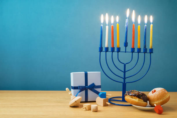 jewish holiday hanukkah background with menorah, sufganiyot, gift box and spinning top on wooden table - hanukkah stock pictures, royalty-free photos & images
