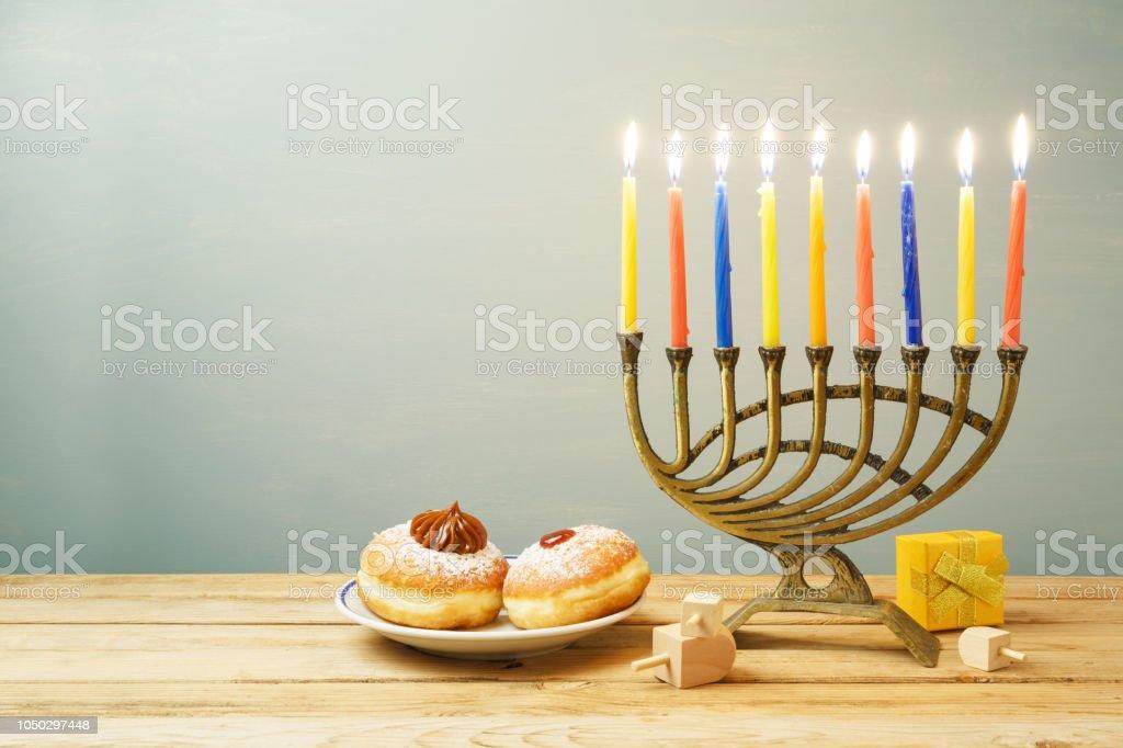 Jewish holiday Hanukkah background with sufganiyot and menorah on...