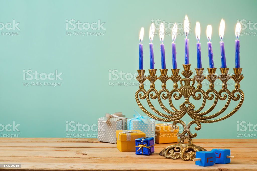 Jewish holiday Hanukkah background with vintage menorah and gift boxes on wooden table stock photo