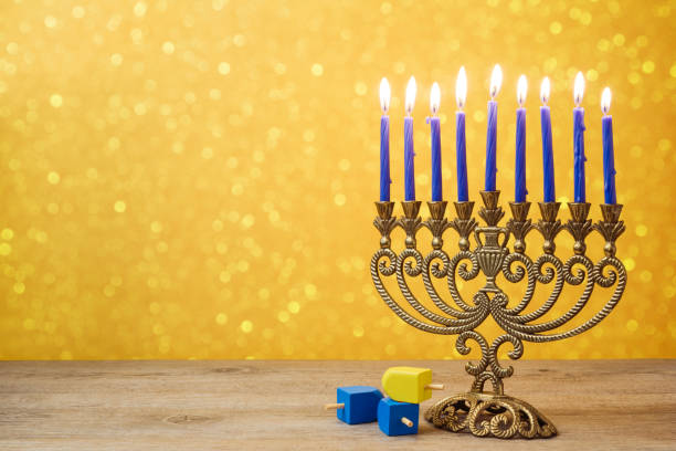 Jewish holiday Hanukkah background with vintage menorah and spinning top dreidel over lights bokeh. stock photo