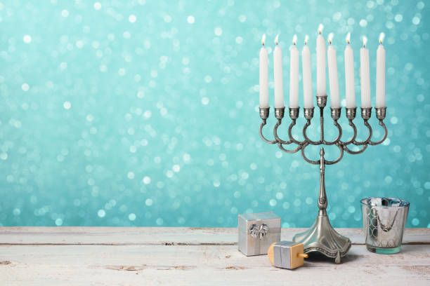 Jewish holiday Hanukkah celebration with menorah, dreidel and gifts on wooden table stock photo
