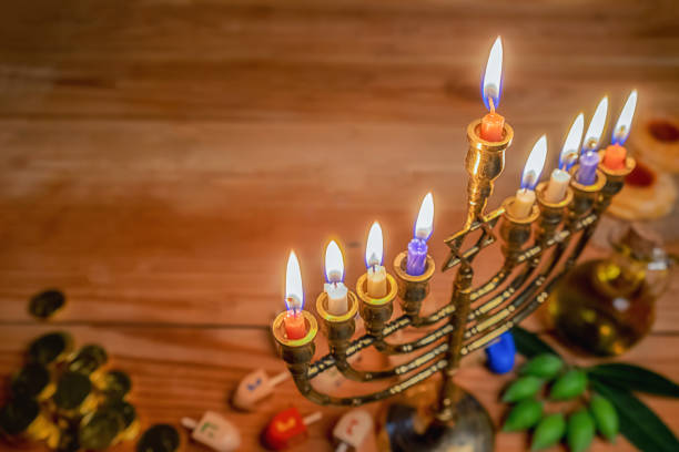 Jewish holiday hanukkah celebration with menorah (traditional candelabra), wooden dreidels (spinning top), donut, olive oil and chocolate coins on wooden table. stock photo