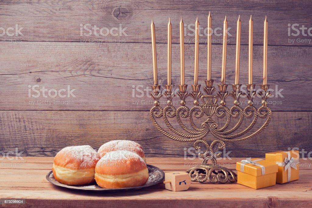 Jewish holiday hanukkah celebration with vintage menorah over wooden background stock photo