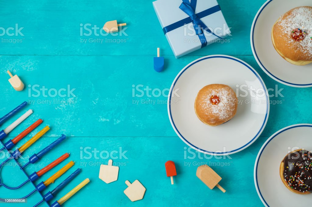 Jewish holiday Hanukkah concept with menorah, sufganiyot, gift box...