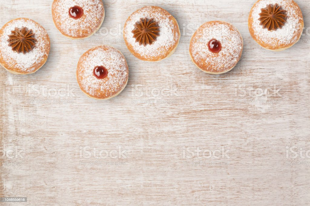 Jewish holiday Hanukkah sufganiyot on wooden background. View from...