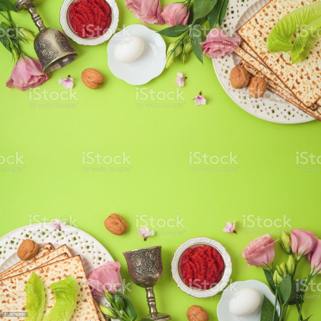 Jewish holiday Passover background with matzo, seder plate and spring flowers. stock photo