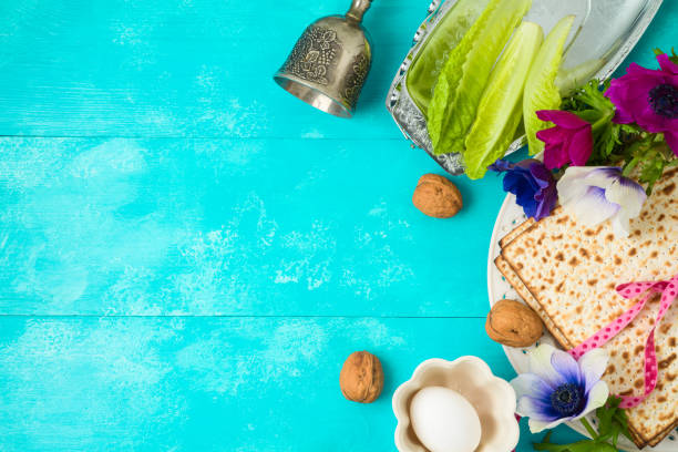 Jewish holiday Passover background with matzo, seder plate and spring flowers on wooden table. Jewish holiday Passover background with matzo, seder plate and spring flowers on wooden table. Top view from above. passover stock pictures, royalty-free photos & images