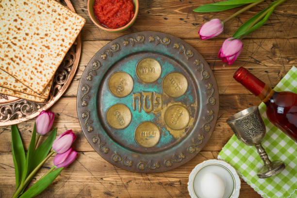 Jewish holiday Passover background with matzo, seder plate, wine and tulip flowers on wooden table. Jewish holiday Passover background with matzo, seder plate, wine and tulip flowers on wooden table. Top view from above. passover stock pictures, royalty-free photos & images