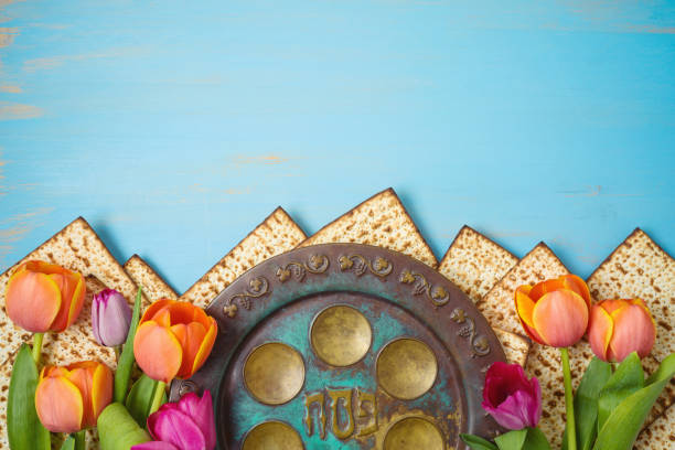 Jewish holiday Passover celebration concept with seder plate, matzah and tulip flowers on wooden table. Pesach background. Jewish holiday Passover celebration concept with seder plate, matzah and tulip flowers on wooden table. Pesach background. Top view from above. seder plate stock pictures, royalty-free photos & images