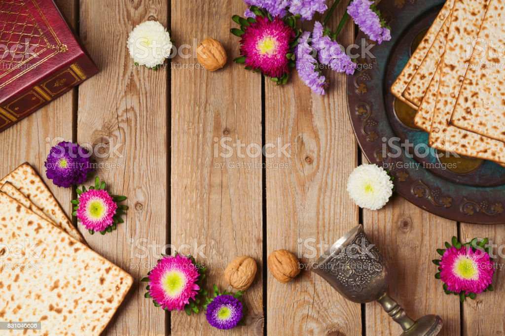 Jewish holiday Passover concept with matza and seder plate over wooden background. View from above stock photo