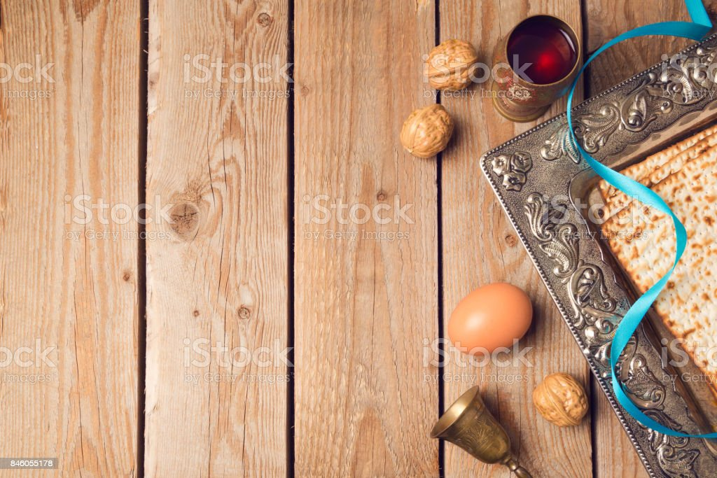 Jewish holiday Passover concept with matzah, seder plate and wine on wooden background. View from above stock photo
