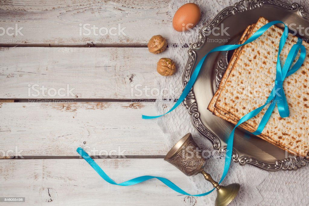Jewish holiday Passover concept with matzah, seder plate and wine glass on white table background. View from above. Flat lay stock photo
