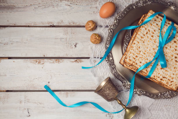 Jewish holiday Passover concept with matzah, seder plate and wine glass on white table background. View from above. Flat lay Jewish holiday Passover concept with matzah, seder plate and wine glass on white table background. View from above. Flat lay passover stock pictures, royalty-free photos & images