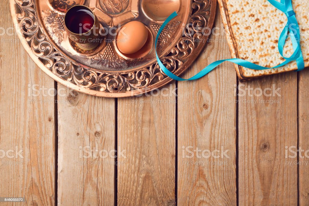 Jewish holiday Passover concept with matzah, seder plate, egg and wine on wooden background. View from above stock photo