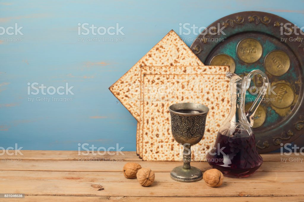 Jewish holiday Passover concept with wine, matza and seder plate on wooden table stock photo