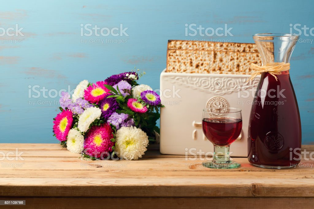 Jewish holiday passover concept with wine, matzoh and spring flowers over wooden background stock photo