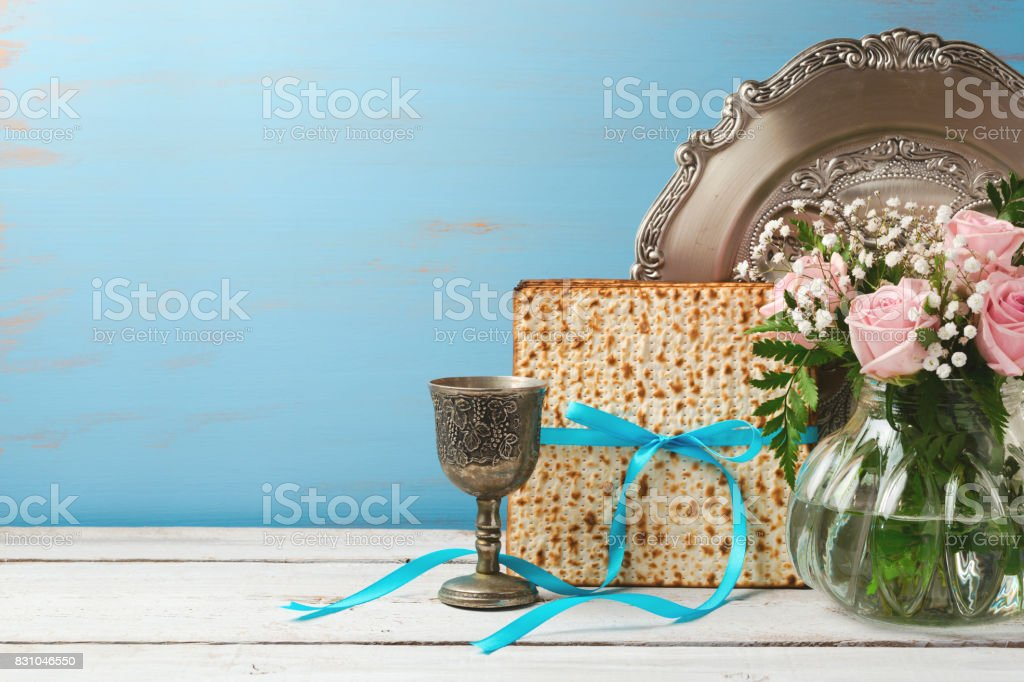 Jewish holiday Passover Pesah background with matzoh, rose flowers and wine glass on wooden table with copy space stock photo
