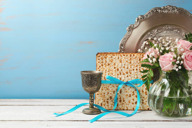 Jewish holiday Passover Pesah background with matzoh, rose flowers and wine glass on wooden table with copy space Jewish holiday Passover Pesah background with matzoh, rose flowers and wine glass on wooden table with copy space passover stock pictures, royalty-free photos & images