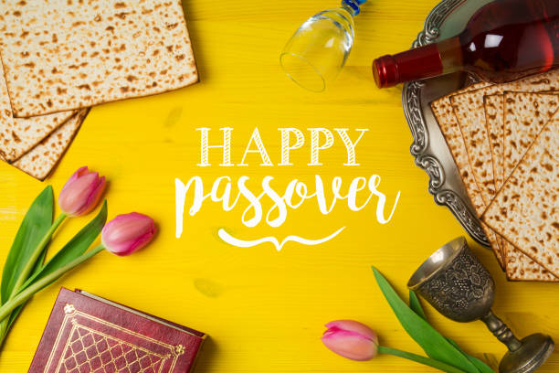 Jewish holiday Passover Pesah celebration with matzoh, tulip flowers and wine bottle on yellow wooden background. View from above Jewish holiday Passover Pesah celebration with matzoh, tulip flowers and wine bottle on yellow wooden background. View from above passover stock pictures, royalty-free photos & images