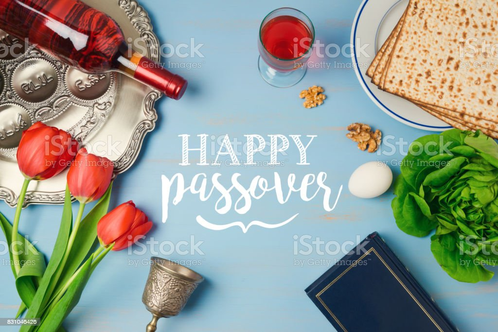 Jewish holiday Passover Pesah greeting card with seder plate, matzoh, tulip flowers and wine bottle on wooden background. View from above stock photo