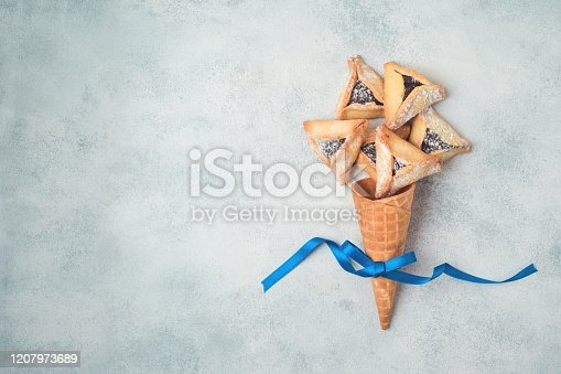 Jewish holiday Purim hamantaschen cookies in waffel cone on rustic background. Top view from above